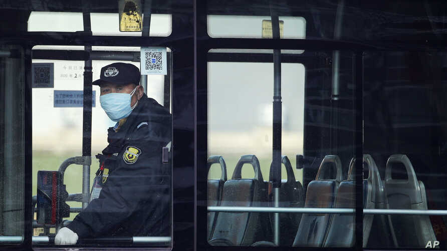 A security guard wearing a mask rides on an empty bus in Beijing, Sunday, Feb. 9, 2020. China's virus death toll on Sunday have surpassed the number of fatalities in the 2002-2003 SARS epidemic, but fewer new cases were reported in a possible sign its spread may be slowing as other nations step up efforts to block the disease. (AP Photo/Andy Wong)